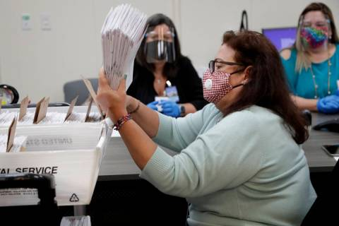 Miami-Dade County Department of Elections employee Elizabeth Prieto gathers vote-by-mail ballot ...