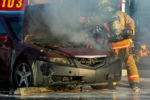 The engine is still on fire as Las Vegas Firefighters cut open the hood in the Mariana's Superm ...