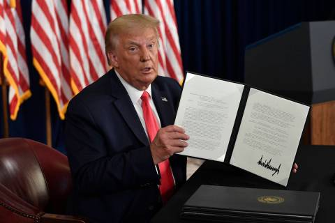 President Donald Trump hold up one of the four executive orders that he signed that addresses t ...