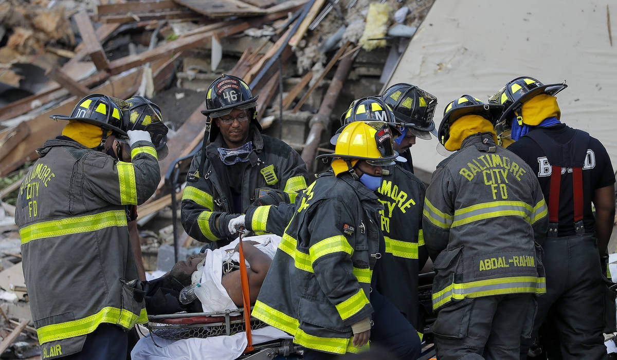 Baltimore City Fire Department carries a person out from the debris after an explosion in Balti ...