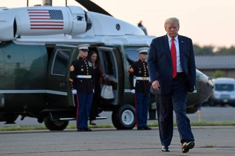 President Donald Trump walks from Marine One and heads over to talk with reporters before depar ...