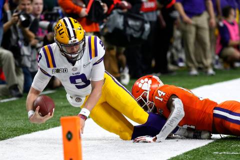 LSU quarterback Joe Burrow is tackled by LSU defensive back Maurice Hampton Jr. during the firs ...