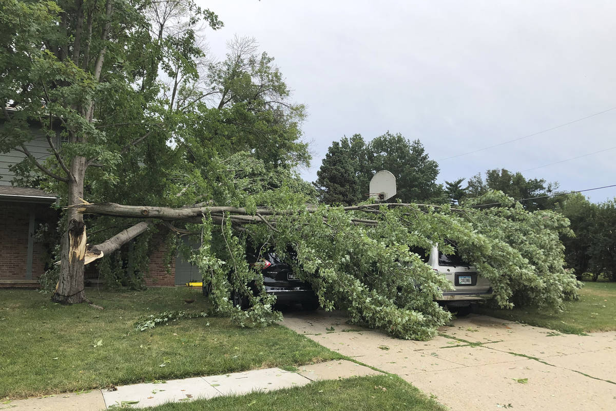 A tree fell across vehicles at a home in West Des Moines, Iowa, after a severe thunderstorm mov ...