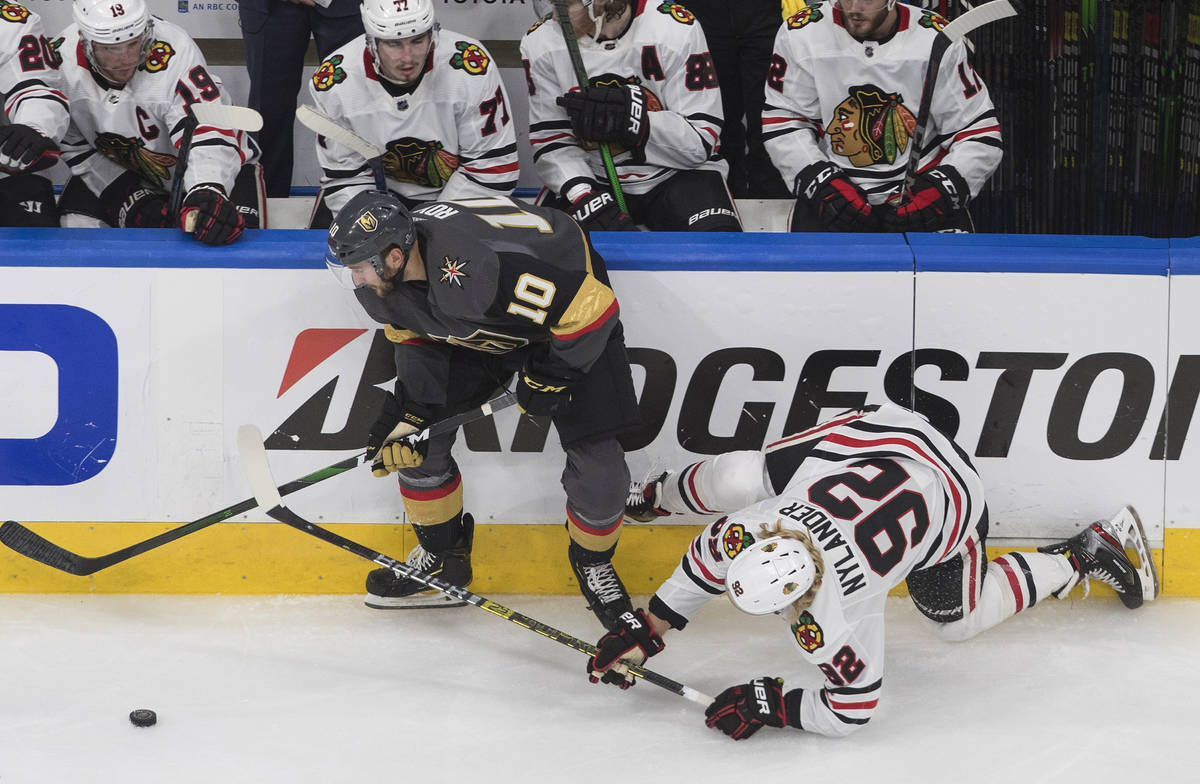 Chicago Blackhawks' Alex Nylander (92) is checked by Vegas Golden Knights' Nicolas Roy (10) dur ...