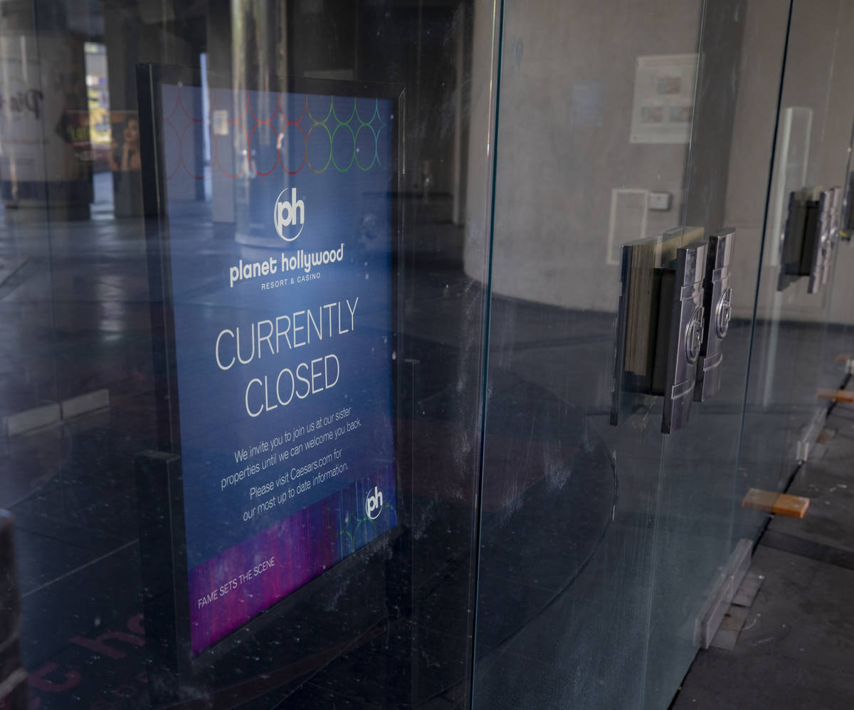 A sign stating Planet Hollywood's temporary closure is seen inside the doors of the hotel-casin ...