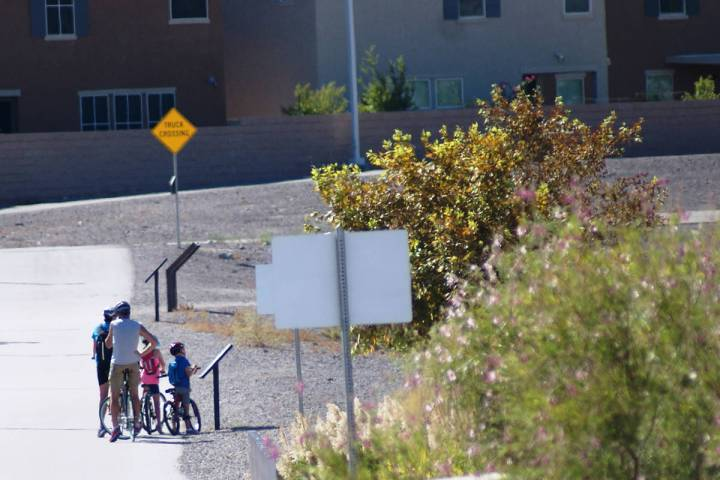 "A family biking at Cornerstone Park stops in late July to read a ""Story Walk"" panel from the hu ..."