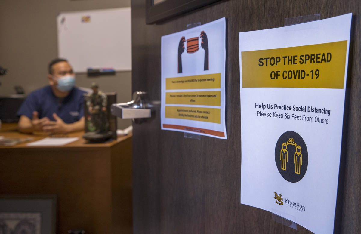 COVID-19 spread literature is taped to the office door of Dr. Hon-Vu Q. Duong who is teaching a ...