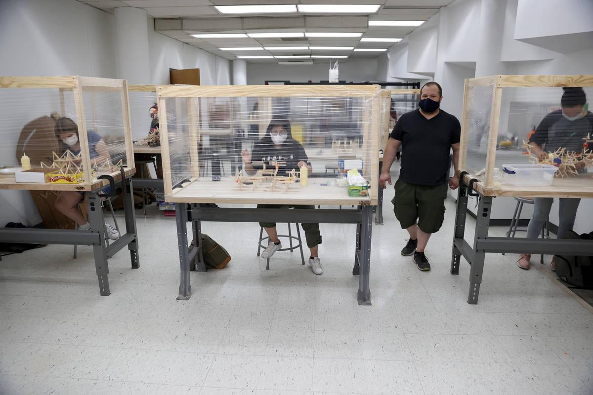 Dave Rowe, associate professor of sculpture practices, walks the classroom during an art class ...