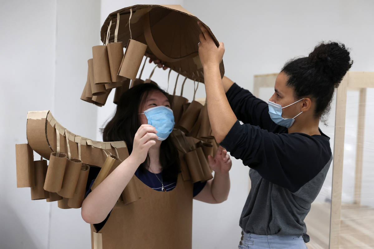 Jessica Yi, left, gets help with putting on a cardboard costume from Tabiya Conyers, during the ...
