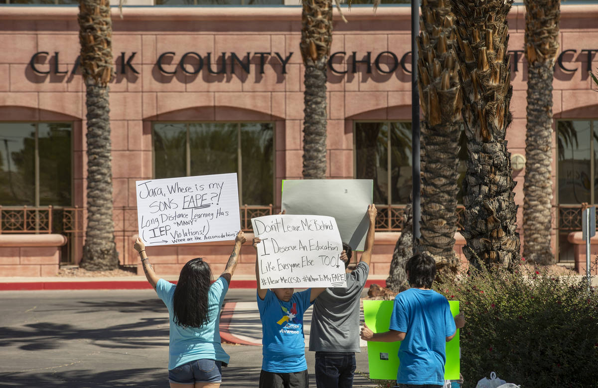 Parent and advocate Yesenia Gonzales, left, hold signs outside the Clark County School District ...