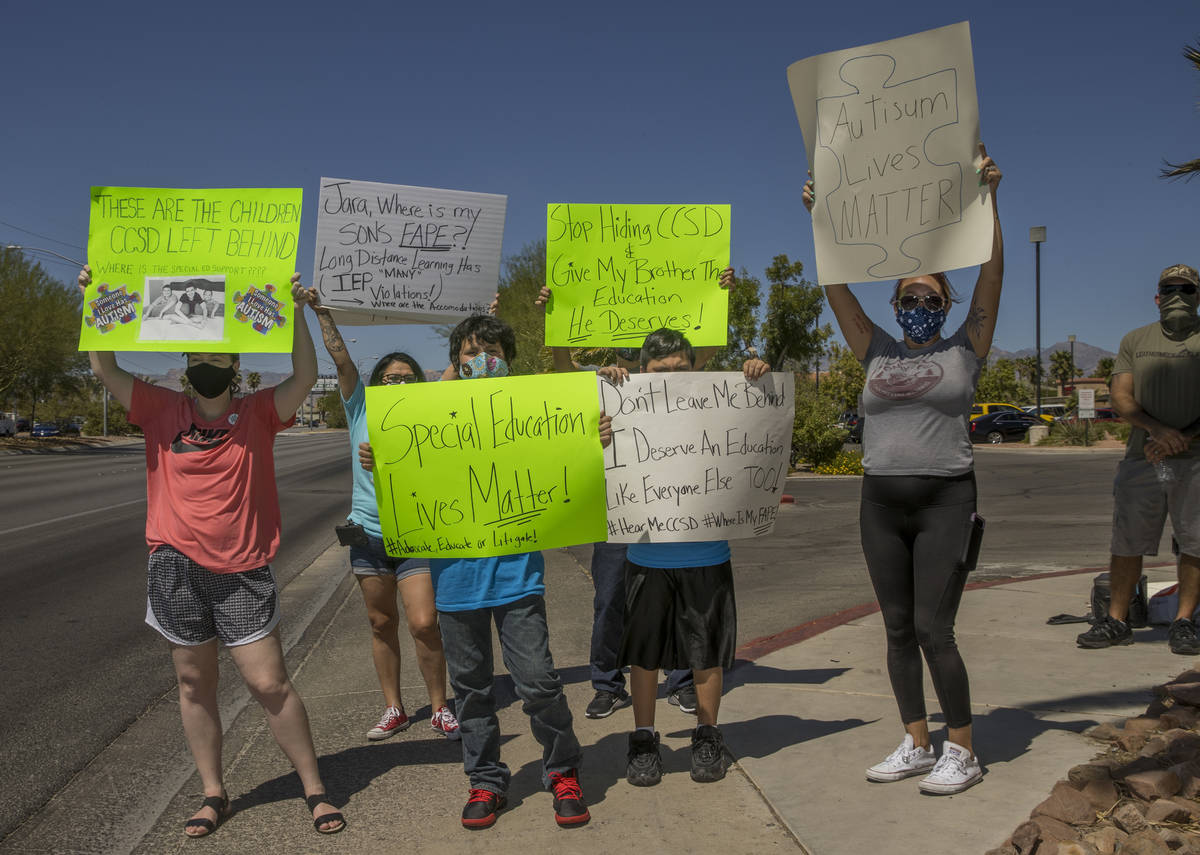 Parents and students stand on the sidewalk outside the County School District Administration Ce ...