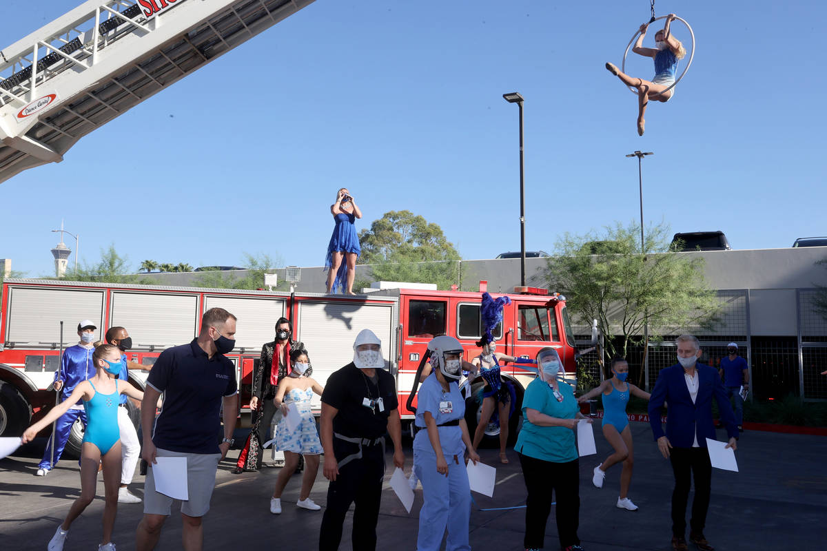 Singer Emily Yates, aerialist Alyssa Gray, other entertainers and medical professionals during ...