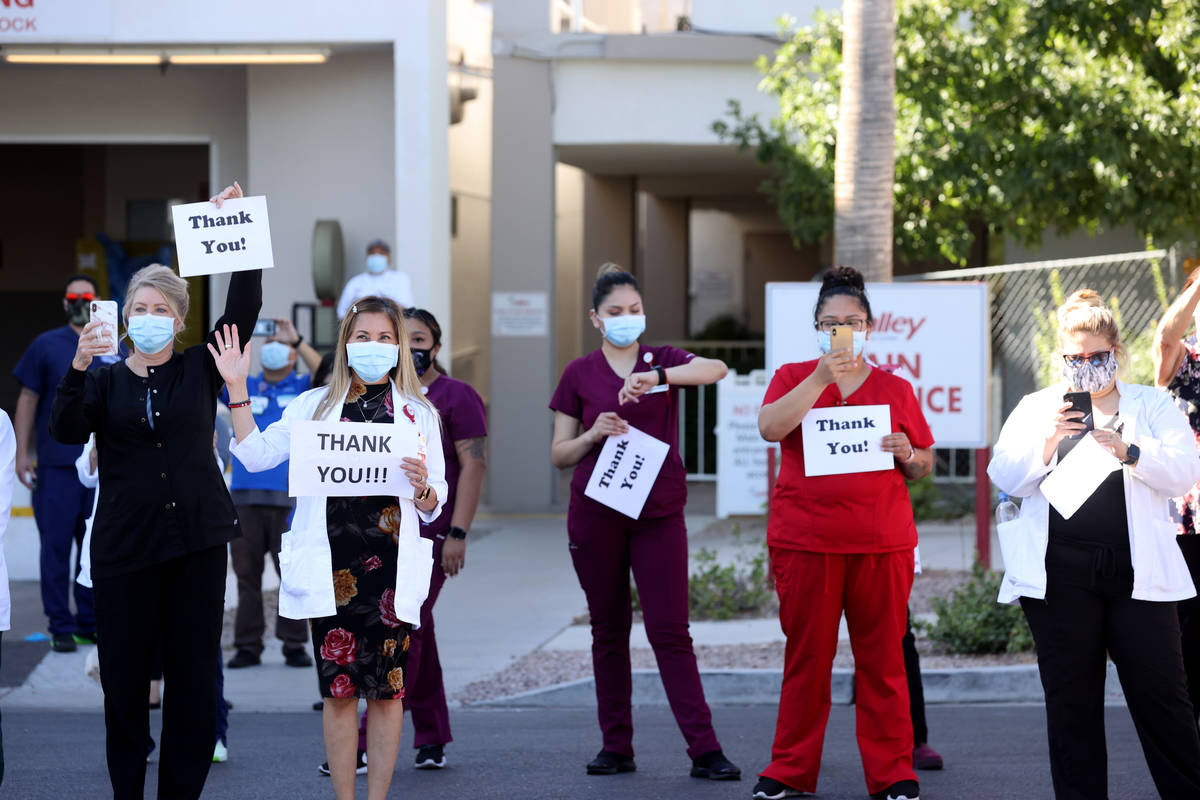 Medical professionals at Valley Hospital Medical Center in Las Vegas, watches a #MaskUpNV show ...