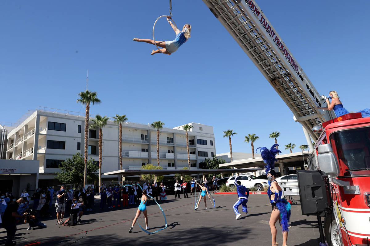 Entertainers, including singer Emily Yates and aerialist Alyssa Gray, perform a #MaskUpNV show ...