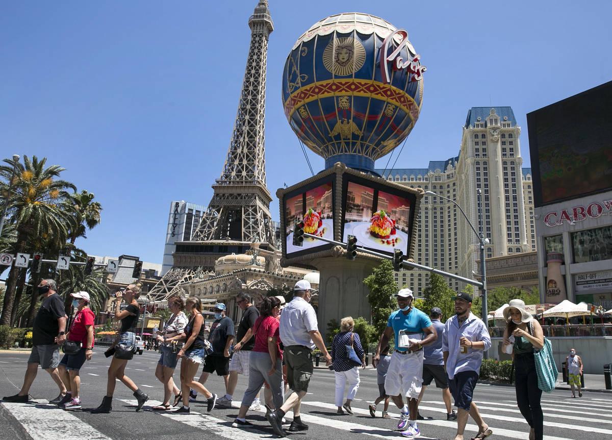 In this July 3, 2020, file photo, tourists cross Las Vegas Boulevard near Paris hotel-casino on ...