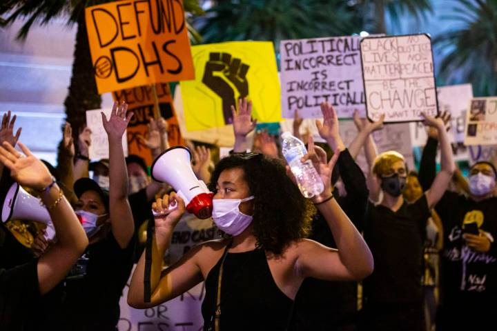 Rally organizer Nakitaa Fletcher holds up her hands as people march for Black Lives Matter and ...