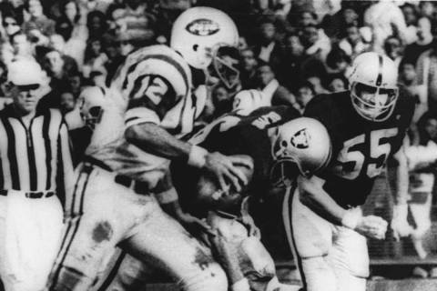 New York Jets' quarterback Joe Namath (12) sweeps around the right side past Oakland defenders ...