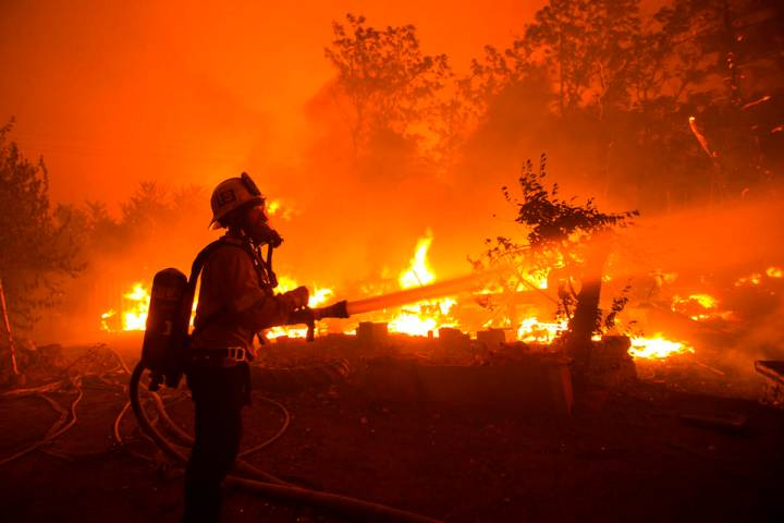 A firefighter works against the Lake Hughes fire in Angeles National Forest on Wednesday, Aug. ...
