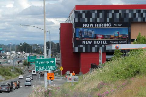 "In this July 9, 2020, file photo, a large video display reads ""Now hiring for our new hotel com ..."