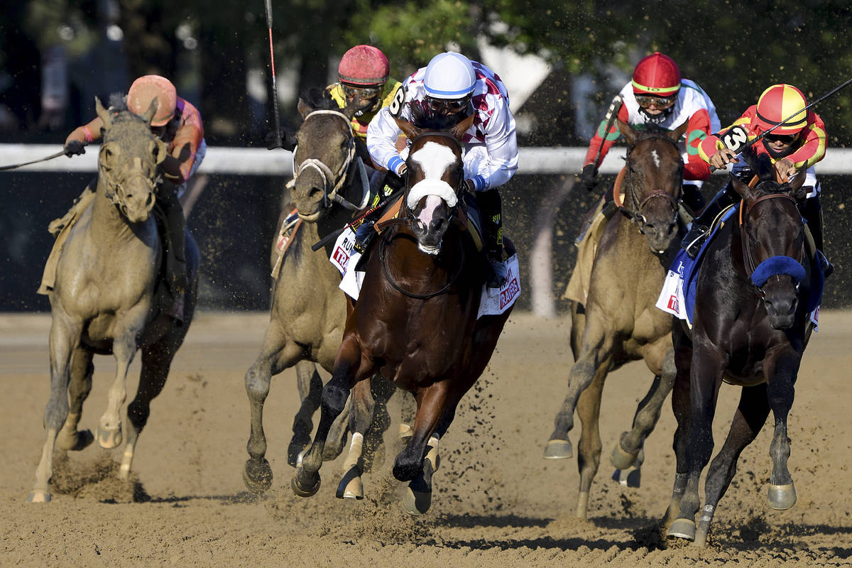 Tiz the Law, with Manny Franco up, center, leads the pack around the final turn on his way to w ...