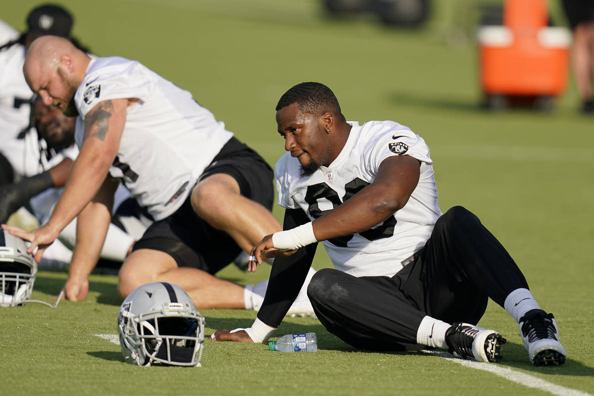 Las Vegas Raiders defensive end Clelin Ferrell, right, stretches during an NFL football trainin ...