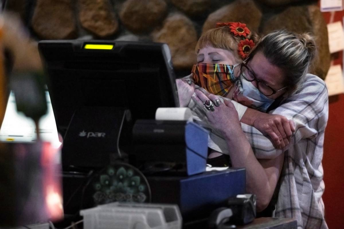 Bartenders Teah Heath, left, and Dawn Smith share a hug minutes before last call at Jackson&#x2 ...