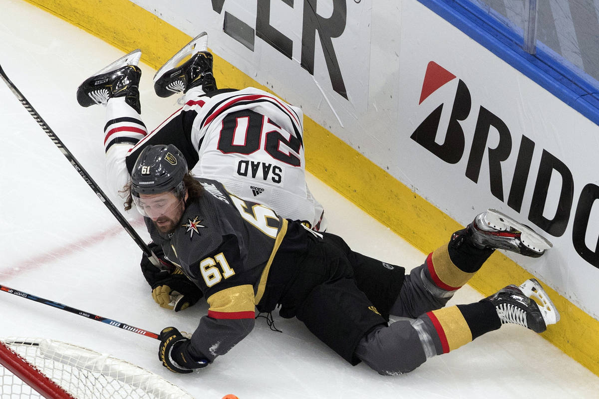 Vegas Golden Knights' Mark Stone (61) lands on top of Chicago Blackhawks' Brandon Saad (20) dur ...