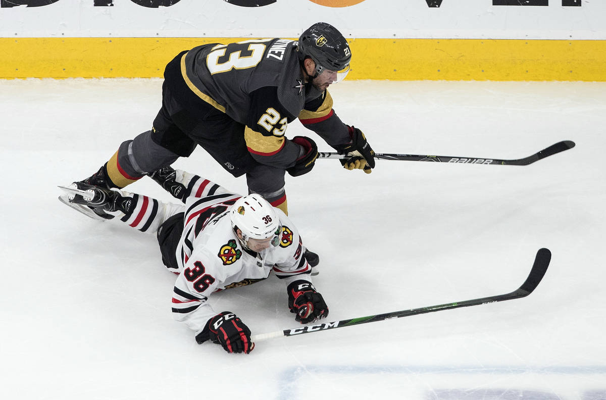 Vegas Golden Knights' Alec Martinez (23) checks Chicago Blackhawks' Matthew Highmore (36) durin ...
