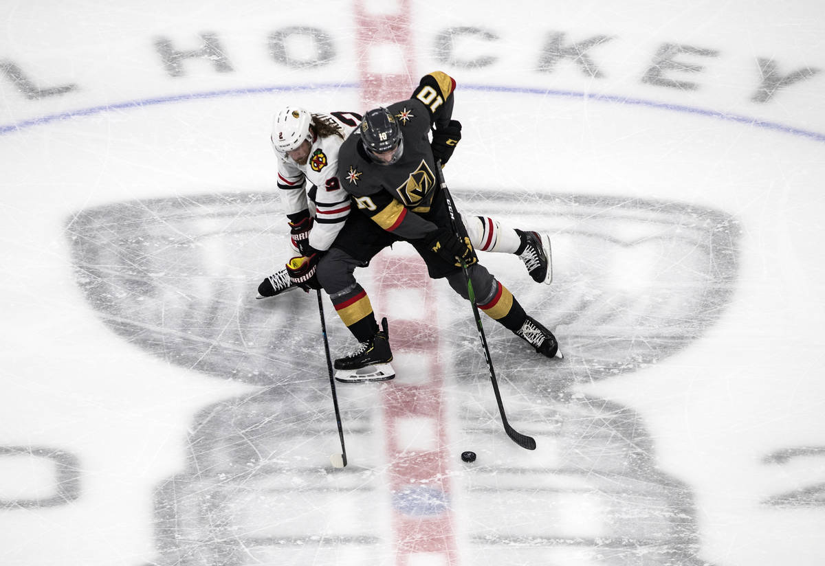 Vegas Golden Knights' Nicolas Roy (10) and Chicago Blackhawks' Duncan Keith (2) battle for the ...