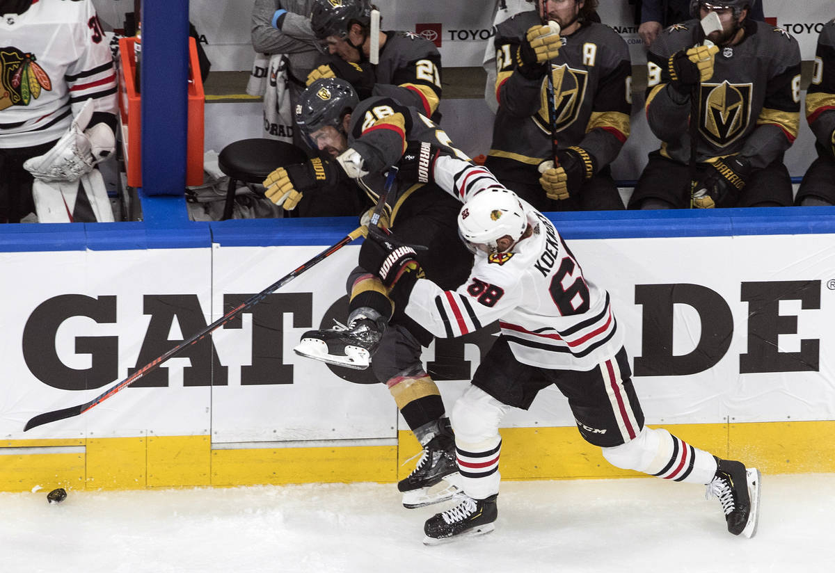 Vegas Golden Knights' William Carrier (28) is checked Chicago Blackhawks' Slater Koekkoek (68) ...