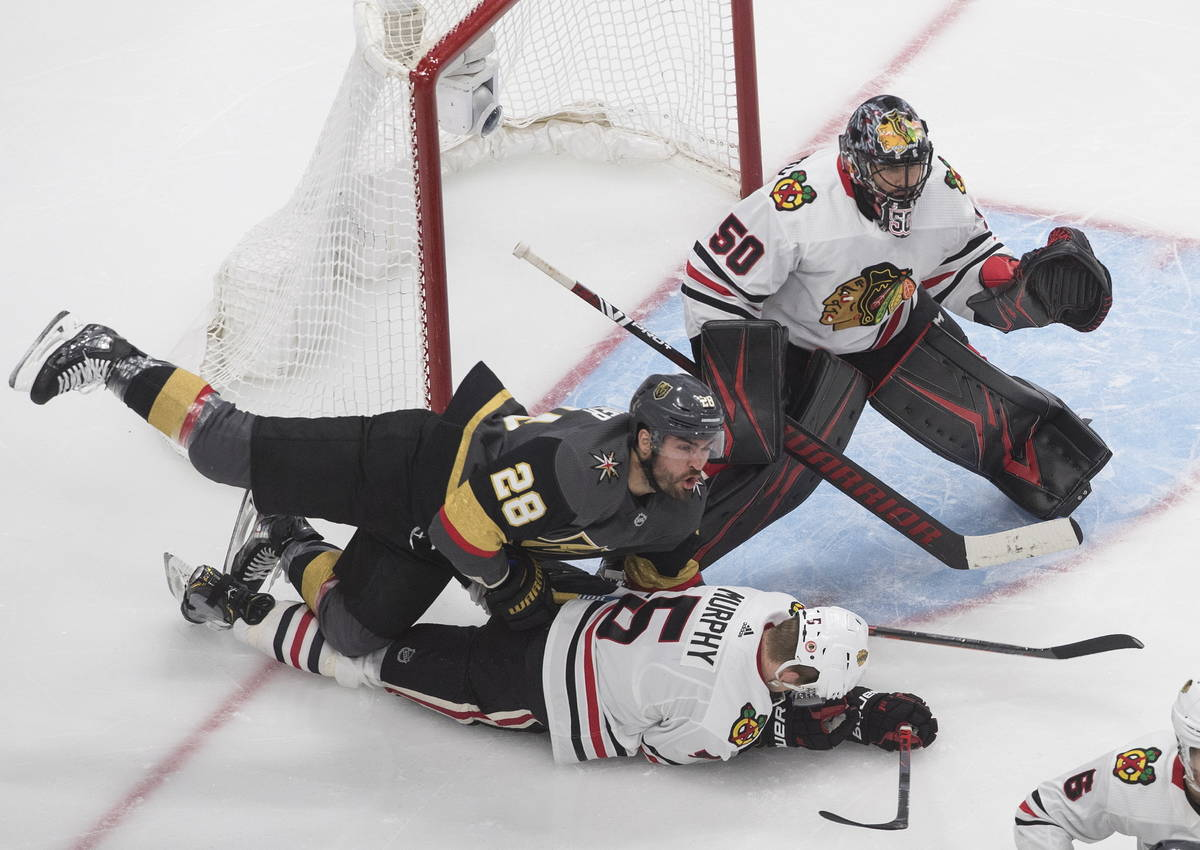 Vegas Golden Knights' William Carrier (28) and Chicago Blackhawks' Connor Murphy (5) battle as ...