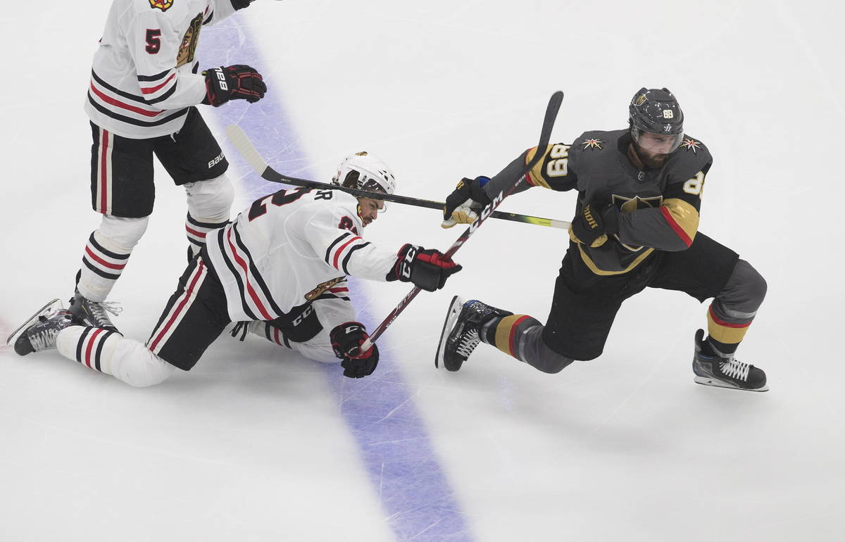 Vegas Golden Knights' Alex Tuch (89) and Chicago Blackhawks' Ryan Carpenter (22) battle for the ...