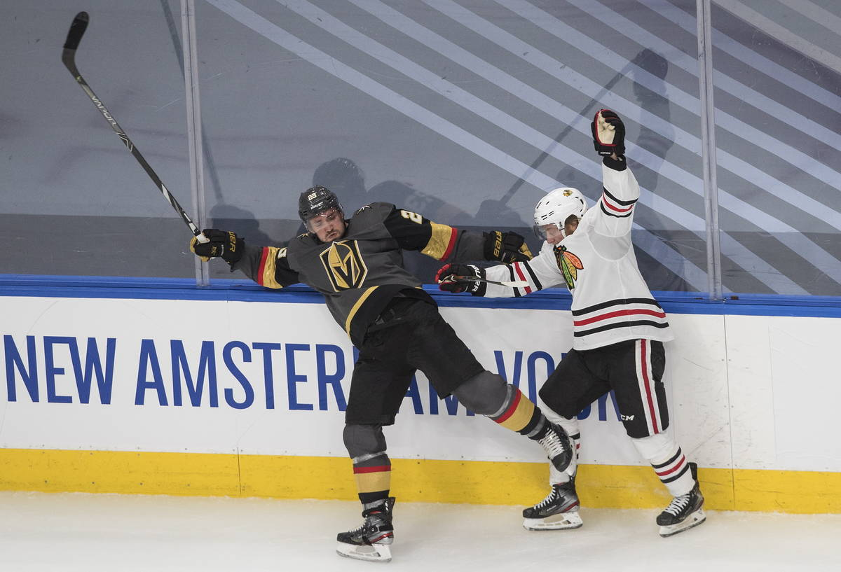 Vegas Golden Knights' Alec Martinez (23) is checked by Chicago Blackhawks' Drake Caggiula (91) ...