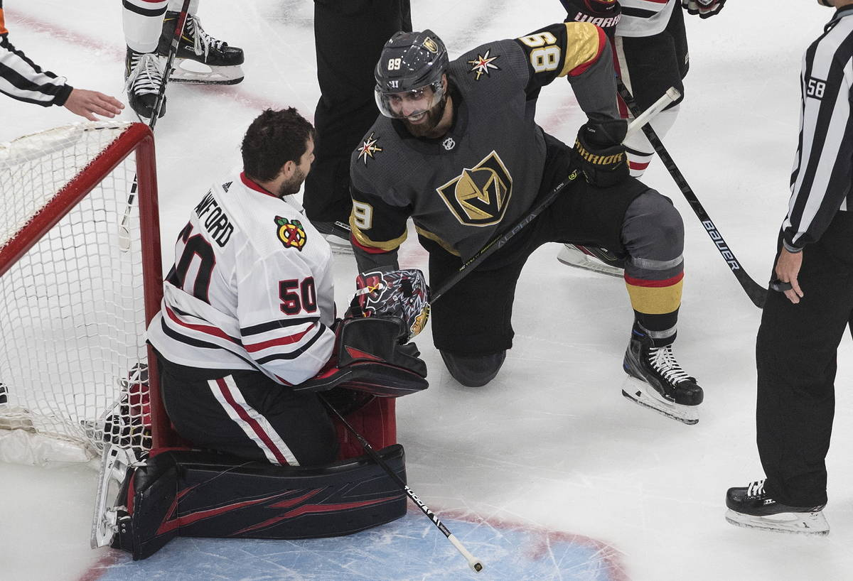 Vegas Golden Knights' Alex Tuch (89) and Chicago Blackhawks goalie Corey Crawford (50) have a l ...