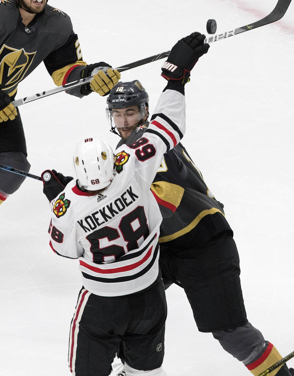 Vegas Golden Knights' Nicolas Roy (10) and Chicago Blackhawks' Slater Koekkoek (68) reach for t ...