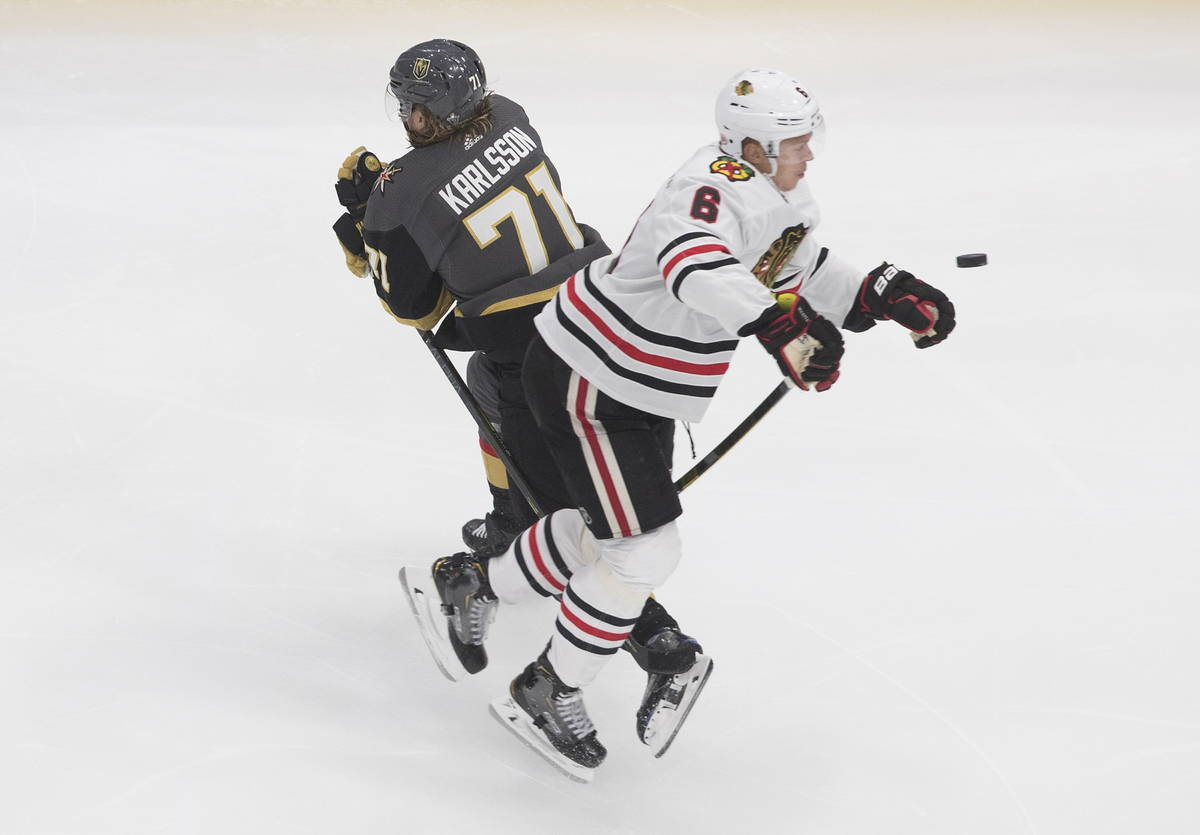 Vegas Golden Knights' William Karlsson (71) and Chicago Blackhawks' Olli Maatta (6) battle for ...