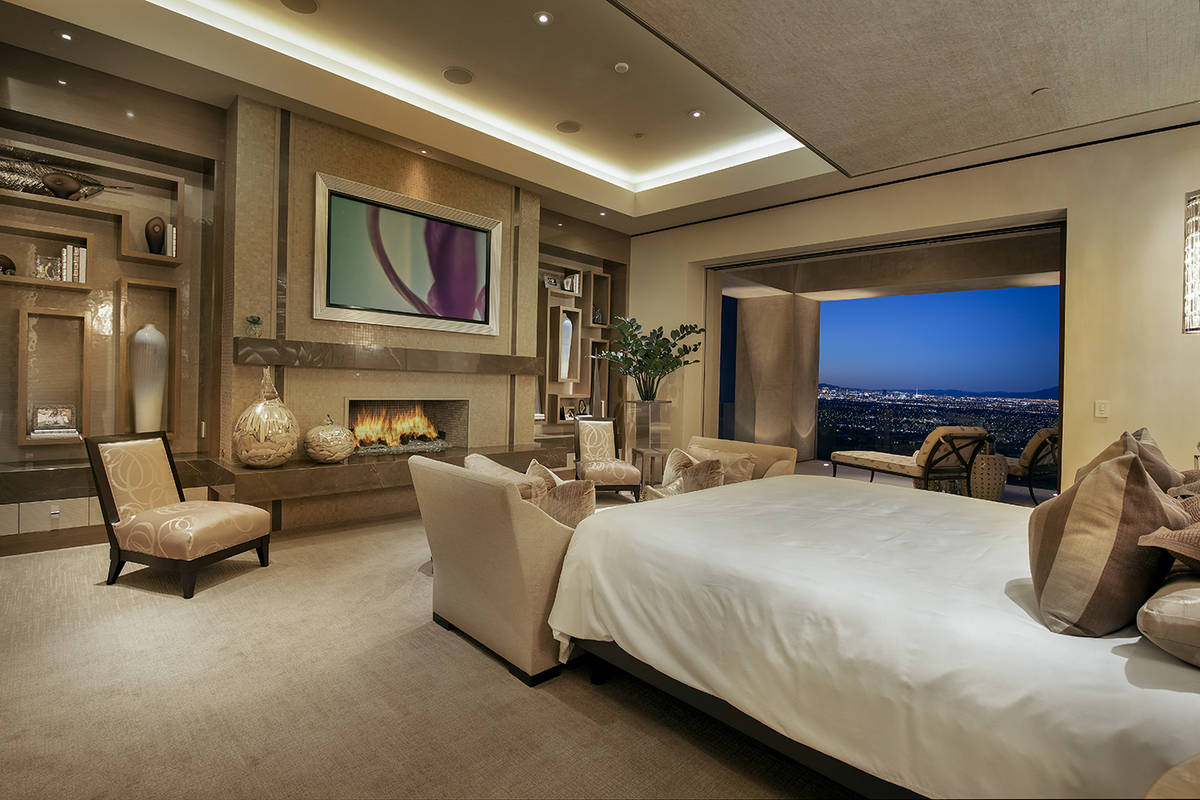The master bedroom, which opens to a patio, has a large setting area and fireplace. The bed's h ...