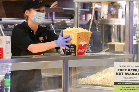 A Cinemark employee prepares popcorn. Five Century-branded movie theaters operated by Cinemark ...