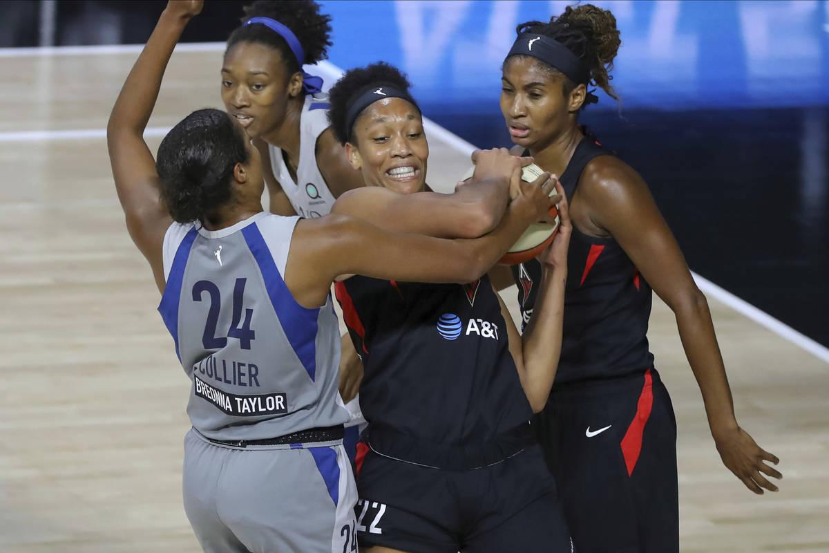 Las Vegas Aces' A'ja Wilson (22) fights for the ball with Minnesota Lynx's Napheesa Collier (24 ...
