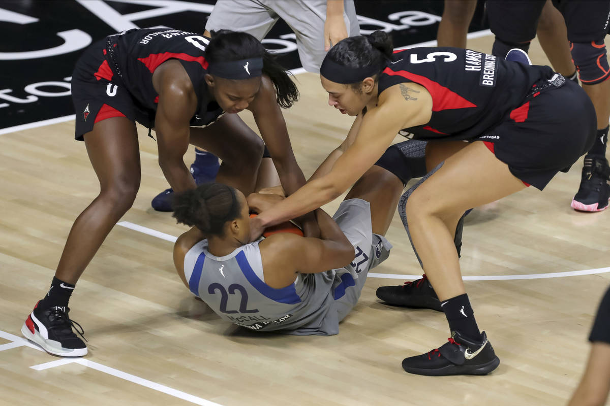 Minnesota Lynx's Erica McCall (22) tries to keep the ball away from Las Vegas Aces' Jackie Youn ...