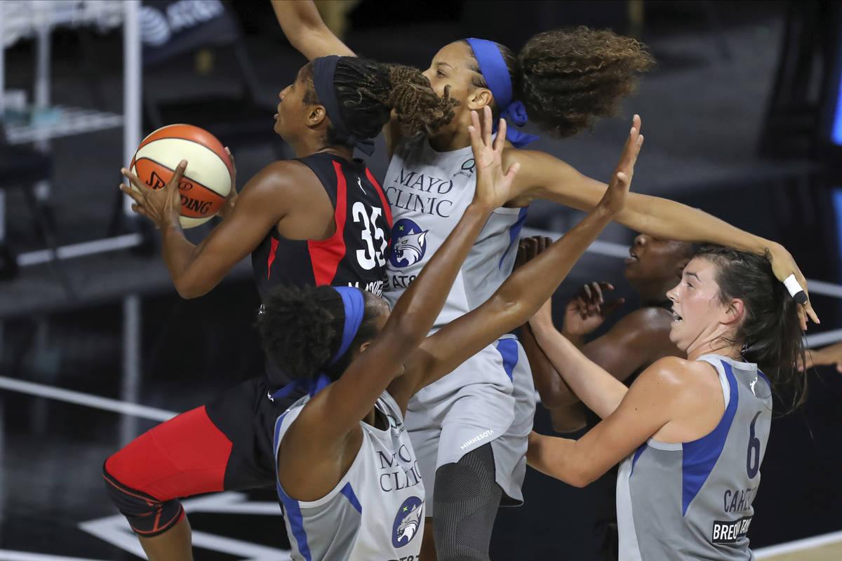 Las Vegas Aces' Angel McCoughtry (35) drives through the Minnesota Lynx defense of, from left t ...