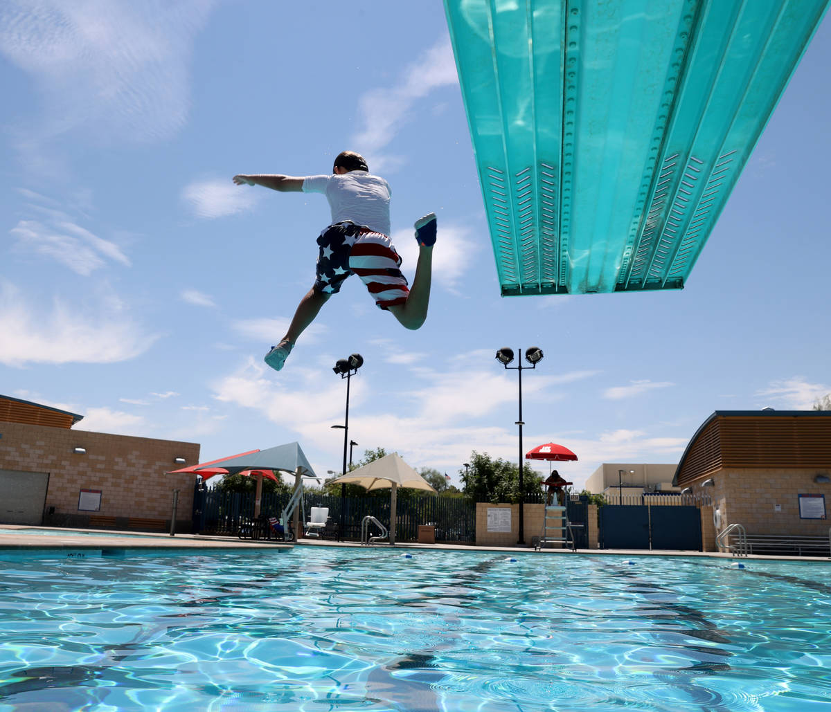 Logan Arnold, 10, of Las Vegas, jumps off the diving board at Garside Pool in Las Vegas Friday, ...