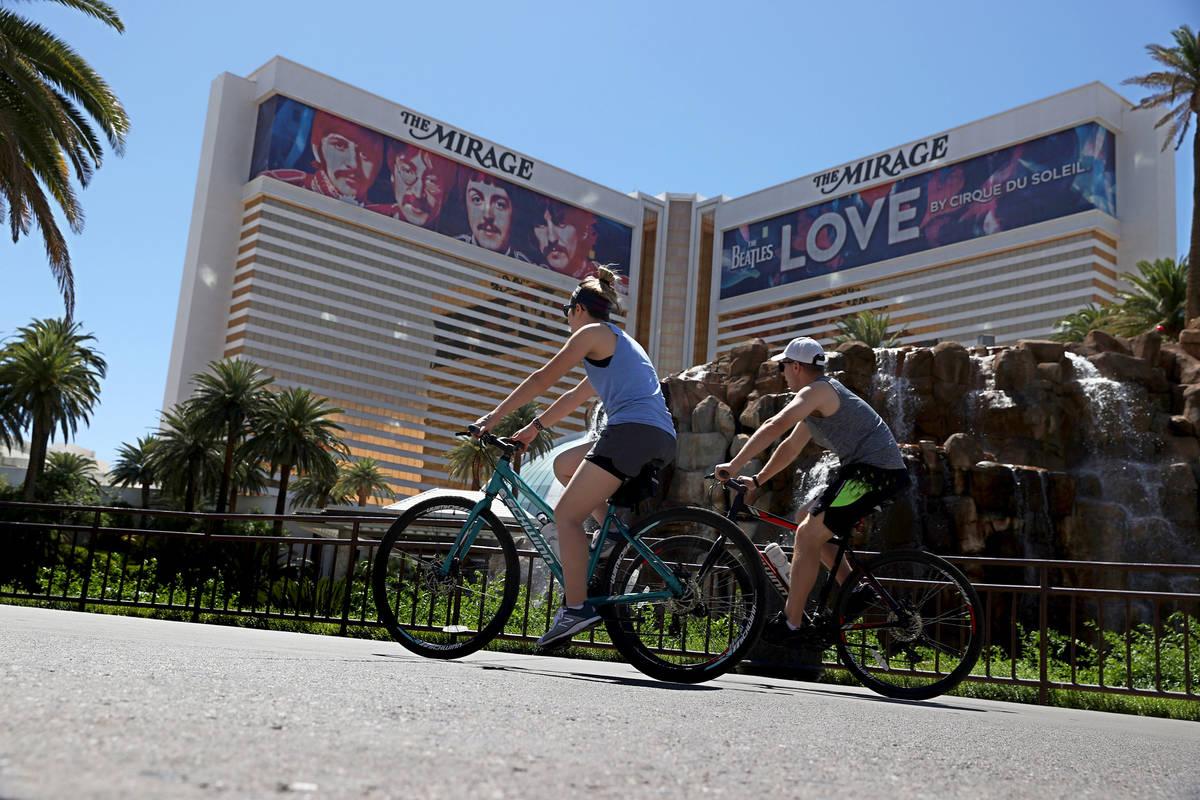 People ride their bikes at the Strip near The Mirage on the Las Vegas Strip, May 23, 2020. (Eri ...
