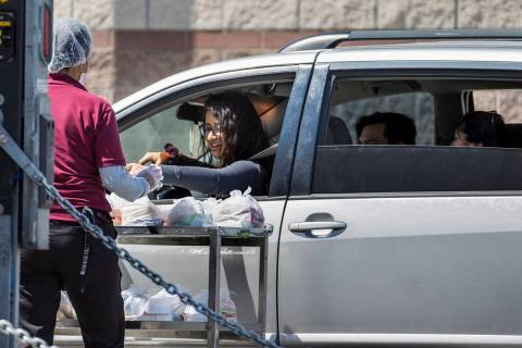 A Clark County School District worker distributes school food donations for students or parents ...
