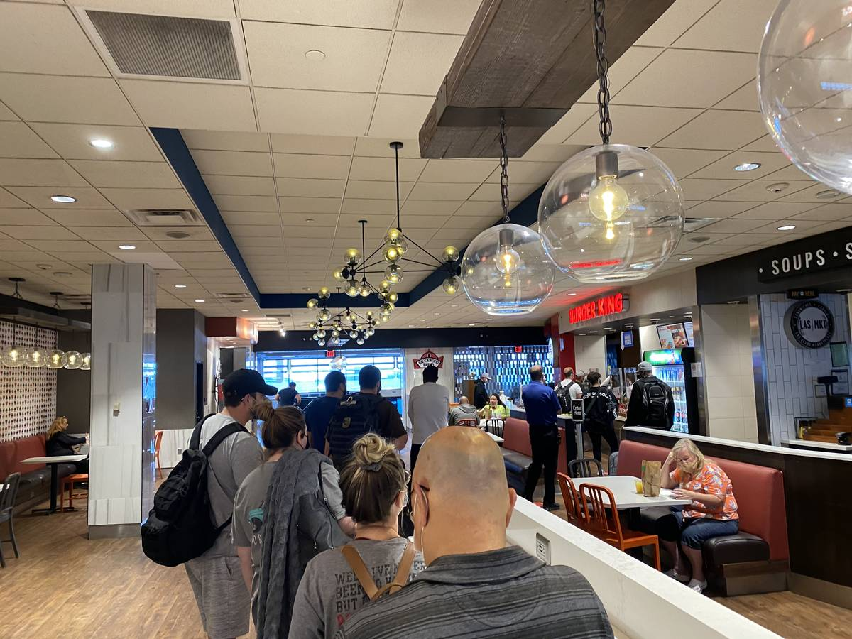 Travelers wait in line at a Burger King in Terminal 1 at McCarran International Airport on July ...