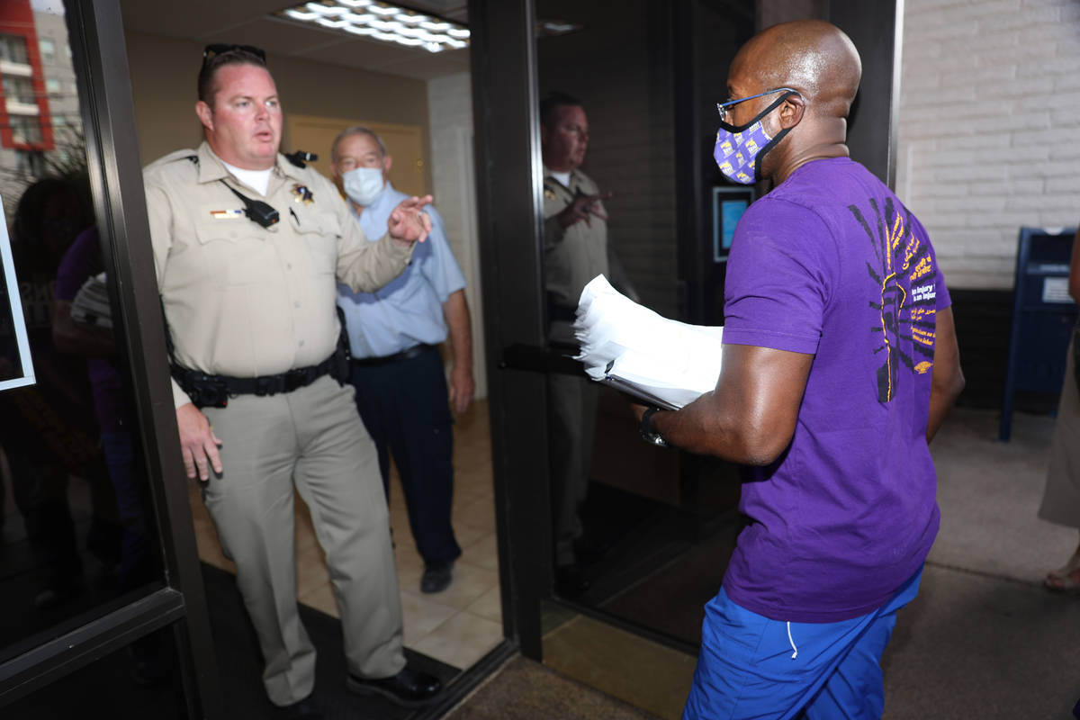 Las Vegas police Sgt. Donald Cox, left, gives directions to SEIU Local 1107 HCA health care wor ...