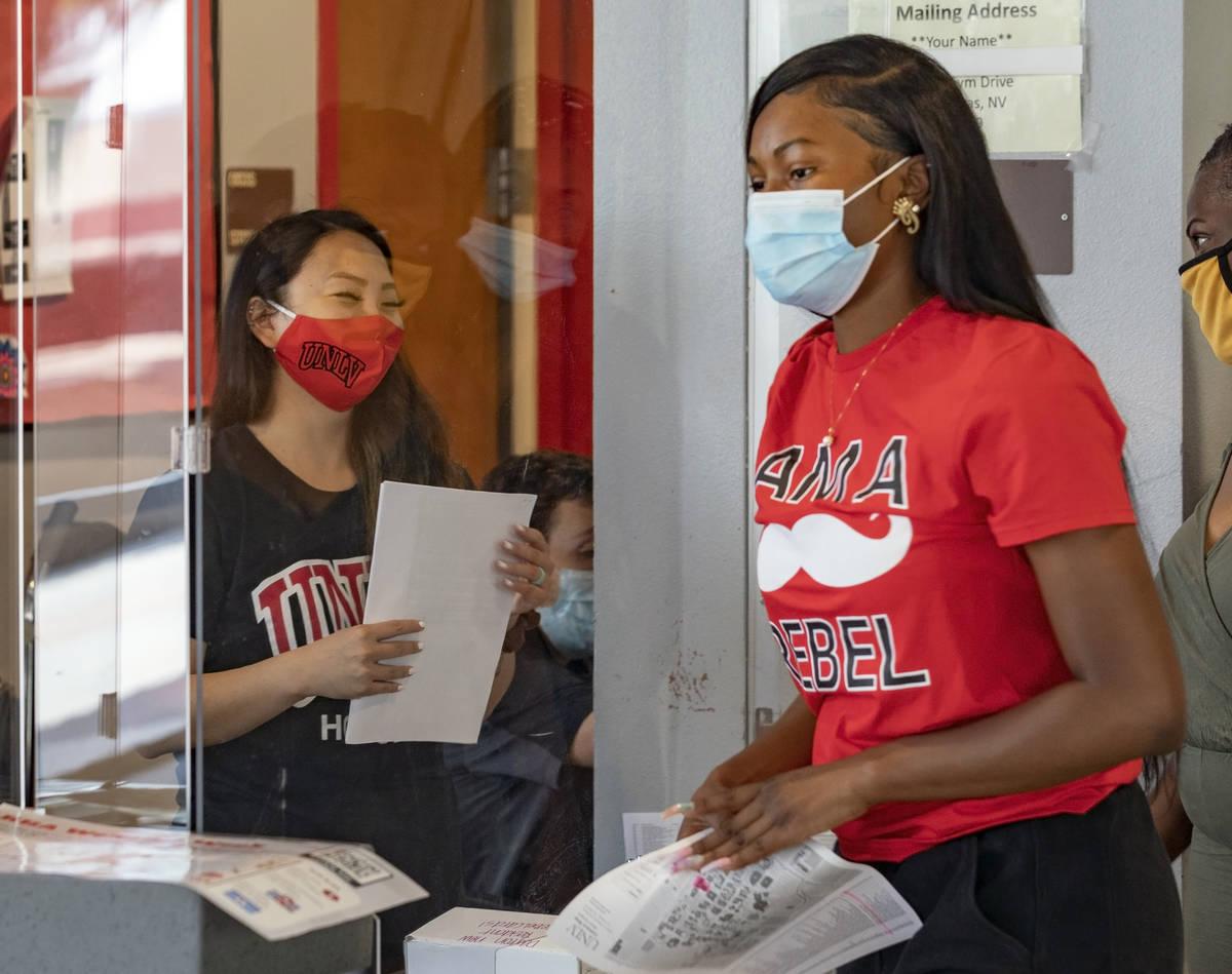 Mail clerk Rachel Deguchi, left, greets UNLV freshman Tyra Bevans, 18, of Los Angeles, during m ...