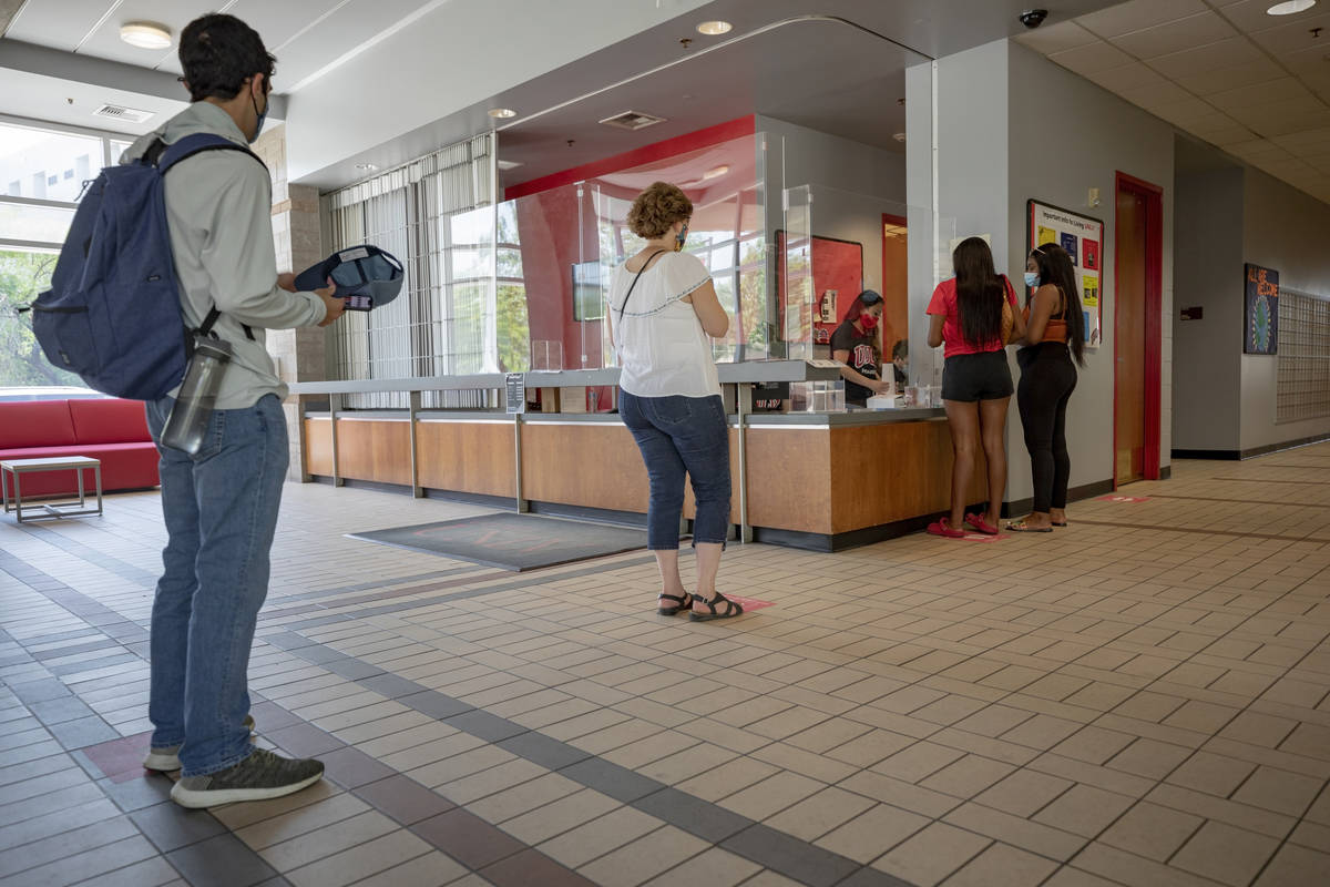 Individuals check-in at Dayton Hall during freshman move-in day at UNLV in Las Vegas on Monday, ...
