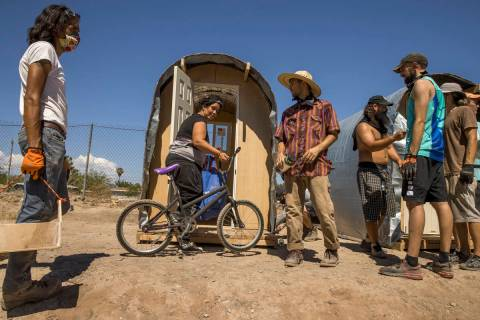 New hut resident Angelica Peacock, center left, looks on as members of Food Not Bombs and the S ...