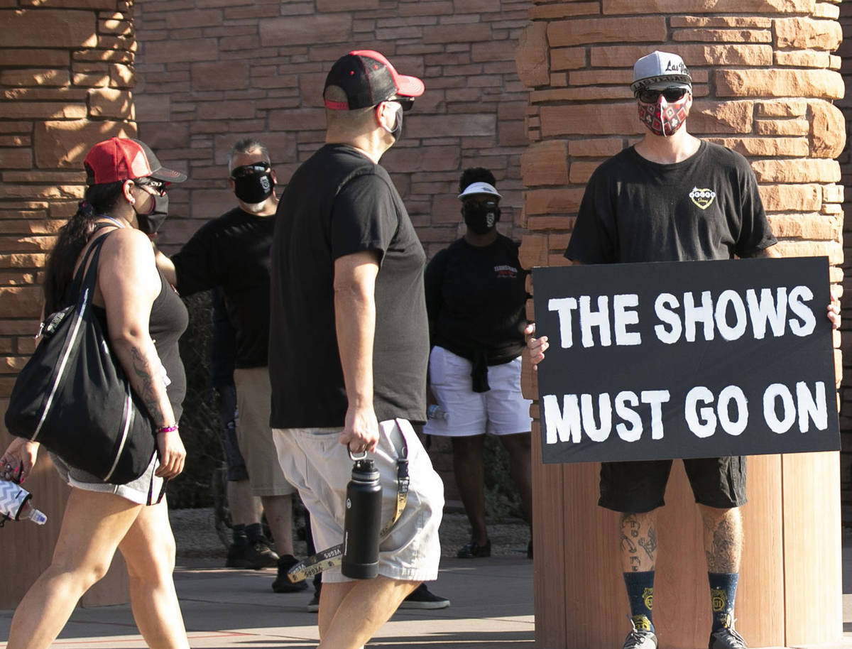 Chaizer Rhodes, trade show worker, holds a sign outside of the Clark County Commission Building ...